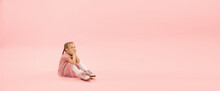 Dreamful Baby. Childhood And Dream About Big And Famous Future. Pretty Girl On Coral Pink Studio Background. Childhood, Dreams, Imagination, Education, Facial Expression, Emotions Concept. Flyer