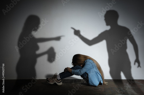 Domestic physical violence, abusing. Scared little caucasian girl, victim sitting close to white wall with shadow of angry threatening parents with alcohol addiction. Awareness of social problem. © master1305