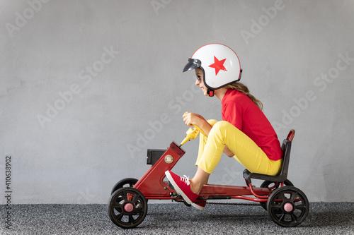 Fotografia Funny kid driving racing car