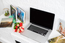 Laptop On White Shelf With Flowers. Tulips, Photo Book.
