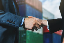 Businessmen Agreement Handshake At Industrial Container Port. Maritime Transport And Export Import Business Concept