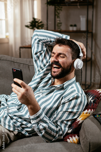 Young man with headphones resting on sofa Fototapet