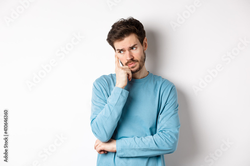 Obraz Worried young man with beard in sweatshirt, looking away pensive and thinking, standing troubled against white background - fototapety do salonu
