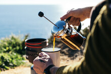 Hipster Millennial Man With Hand Tattoos Prepare Specialty Coffee In French Press, Use Camping Stove And Enamel Cup. Good Filter Coffee During Camping Trip