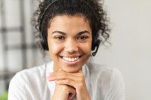 Headshot Of Friendly African American Millennial Woman In A Headset Sitting With Her Hands On A Chin, Working In The Customer Service Department As Call Center Operator, Helping Client With Inquiry