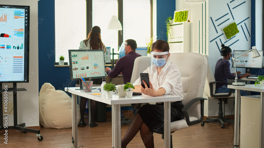 Fototapeta Entrepreneur wearing visor against coronavirus using phone with wireless headphone for videocall talking with remotely team sitting in new normal office. Colleagues working respecting social distance