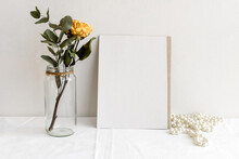 Fashionable Stock Stationery Background - White Card For Lettering And Dry Yellow Roses On A White Table. Wedding Feminine Background. Blank For An Invitation Card.
