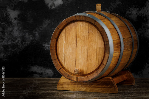 Valokuva A beautiful wooden barrel and a worn oak wood table set against a dark wall patt