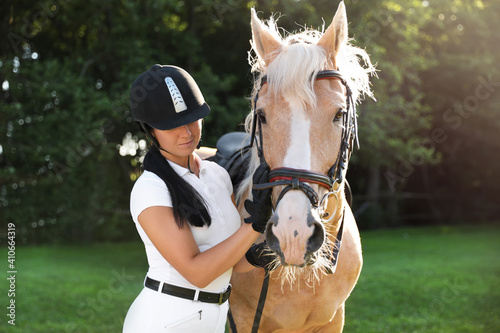 Fototapeta Young woman in horse riding suit and her beautiful pet outdoors on sunny day