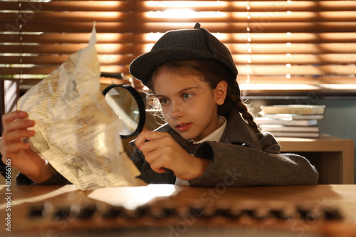 Obraz na plátně Cute little detective exploring document with magnifying glass at table in offic