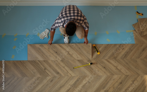 Obraz Professional worker installing new parquet flooring indoors, top view - fototapety do salonu