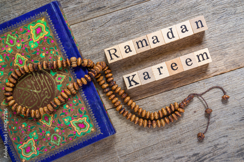 Stampa su Tela Holy Al Quran with written arabic calligraphy meaning of Al Quran and rosary beads or tasbih on shabby wooden board