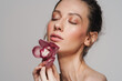 Sensual half-naked woman posing with orchid on camera