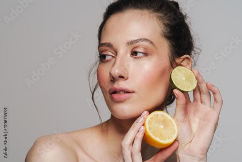 Obraz Beautiful half-naked woman posing with citruses on camera - fototapety do salonu