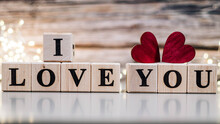 Wooden Cubes With I LOVE YOU Message With Wooden Hearts Isolated On Wood Background. Text I LOVE YOU. Valentines Day Background.