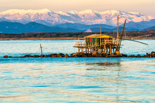 Trebuchet Fishing Hut At Sunset Against The Alps Covered With Snow, Marina Di Pisa, Tuscany, Italy