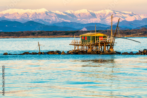 Obraz na plátně Trebuchet fishing hut at sunset against the Alps covered with snow, Marina di Pi