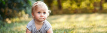Cute Baby Girl Crawling On Ground In Park Outdoors. Adorable Child Toddler Learning To Walk. Healthy Physical Development. Funny Kid. Authentic Lifestyle Happy Childhood. Web Banner Header.