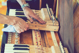 Setting up an old piano. The master repairs an old piano. Deep cleaning the piano. Hands of professional worker repairing and tuning an old piano. toned