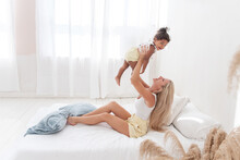 Young Caucasian Blond Mother Plays, Lies On White Bed With African American Daughter Son. Happy Multi Ethnic Family Morning. Woman Hugs, Strokes Children With Tenderness. Minimalistic White Interior