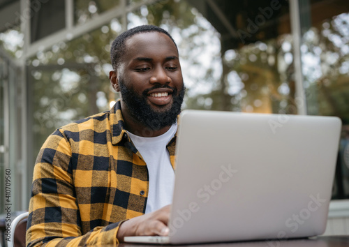 Obraz Smiling copywriter working freelance project, typing on keyboard, sitting at workplace. Portrait of young African American programmer using laptop computer  - fototapety do salonu