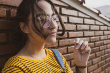 Teenager Girl Wearing Colorful Clothes And Transparent Clear Eyeglasses In Front Of A Red Brown Brick Wall Posing Playing With Her Hair. Downtown City Centre Autumn Concept.