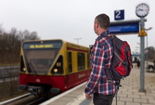 A Hiker With A Backpack Stands On The Platform Of A Regional Train Station In East Berlin And Waits For The Train. The Sky Is Grey. A Train Arrives.