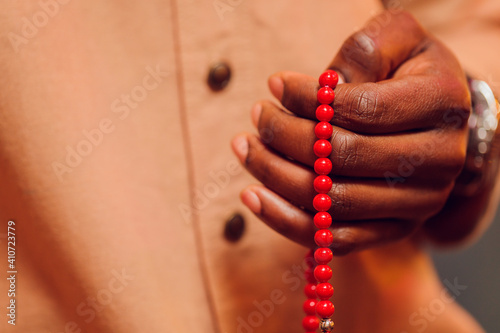 Fotografie, Obraz Hand holding a muslim beads rosary or tasbih on a praying mat, pray to god