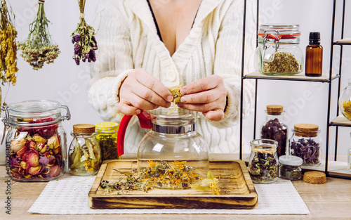 Obraz Close up view of woman herbalist mixing various dried herbs for traditional medicinal tea. Dried herbs in glass jars on background. - fototapety do salonu