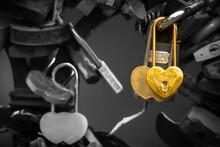Close-up Of Golden, Heart Shaped, Wedding Padlocks Hanging On Bridge Railing. Monochrome Background.