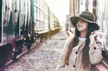 Portrait Of Smiling Woman With Hat And Beige Jacket Leaning Between Two Abandoned Train Cars.
