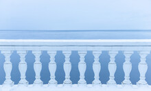 White Balcony Over Winter Sea. Snow-covered Classic Balustrade Against The Blue Sea.