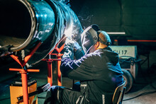 Shallow Focus Of A Welder Wearing A Protective Helmet And Welding Steel In A Factory