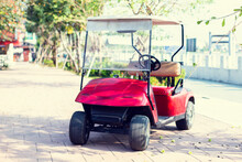Red Colored Golf Cart With Green Tree Background.