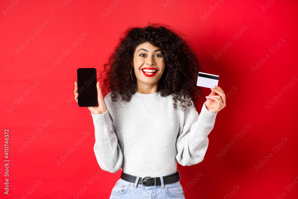 Fototapeta E-commerce and online shopping concept. Cheerful woman smiling, showing plastic credit card and empty smartphone screen, standing on red background