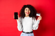 Leinwandbild Motiv E-commerce and online shopping concept. Cheerful woman smiling, showing plastic credit card and empty smartphone screen, standing on red background