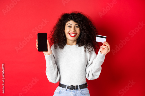 Obraz E-commerce and online shopping concept. Cheerful woman smiling, showing plastic credit card and empty smartphone screen, standing on red background - fototapety do salonu