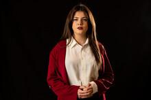 Mujer Joven Y Atractiva Con Camisa Blanca Y Chaqueta Roja Posa Sobre Fondo Negro.