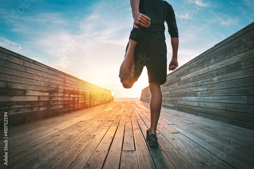 Obraz Young slim sporty man warming and stretching legs before run outdoors at sunset or sunrise. Athletic man in black sportswear doing fitness stretching exercises. Sport and healthy lifestyle. - fototapety do salonu