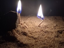Close-up Of Burning Matchsticks On Sand