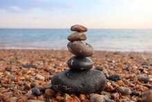 Beautiful Balance Of Stones On The Sandy Beach Of The Ocean, On A Background Of Bright Sky