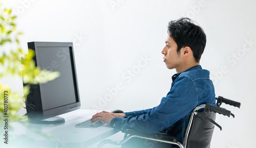 Fotografiet パソコンを使う男性身体障害者・車椅子