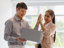 Young Asian Businesspeople Wearing Smart Casual Standing And High Five For Congratulate Happily During Looking On A Computer Laptop. Success Confident And Cheerful Concept