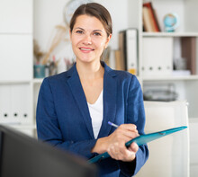 Female Office Worker Is Standing With Documents Before Signing It In Office