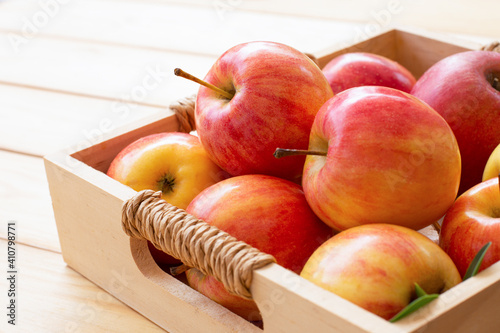 Fototapeta Red organic envy apple in crate isolated on wooden table background