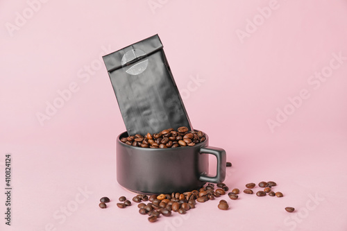 Cup with coffee beans and bag on color background © Pixel-Shot