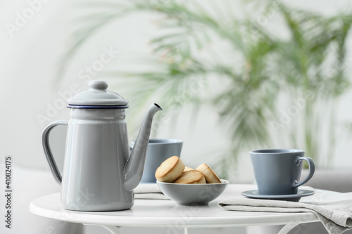 Teapot and cup with tea on table in room © Pixel-Shot