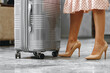 Leinwandbild Motiv Unrecognizable woman in pink dress standing with luggage suitcase