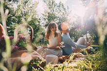 Picnic For Lovers. Happy Young Couple Spend Time Outdoors At Sunset Of The Day. Lovers Have Fun Sitting On The Bedspread In The Forest. Boy And Girl On A Romantic Date At Sunset