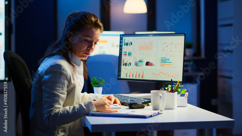 Exhausted manager trying to finish business project respecting deadline working at night in front of computer taking notes writing on notebook. Tired employee overtime sitting at desk in workplace